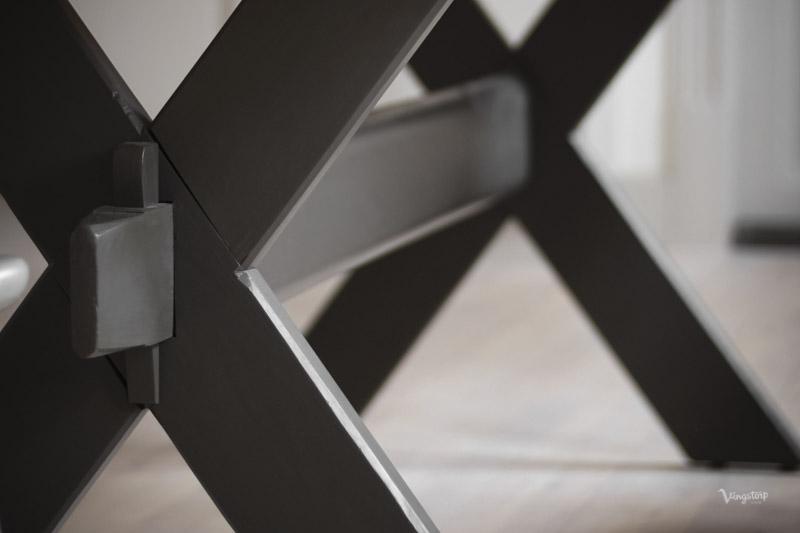 Kryssbord I mörkgrå kulör målad med linoljefärg.